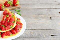 Healthy and quick omelette stuffed with fresh strawberries and garnished with mint on a plate and wooden background. Recipes for kids. Healthy omelette. Kids royalty free stock images