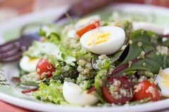 Healthy quinoa salad with tomatoes, avocados, eggs, herbs. Lettuce, lemon, diet dish stock photos