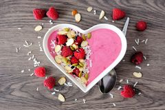 Raspberry smoothie in a heart bowl with superfoods, above on wood. Healthy raspberry smoothie in a heart shaped bowl with superfoods. Above scene on a wood Royalty Free Stock Photos