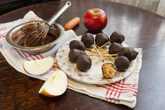 Healthy raw apple and carrot candies on sticks in raw chocolate. On old vintage table Royalty Free Stock Image
