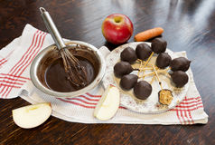 Healthy raw apple and carrot candies on sticks in raw chocolate. On old vintage table Stock Images