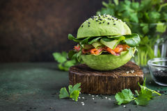 Healthy raw avocado burger with salted salmon and fresh vegetabl Royalty Free Stock Images