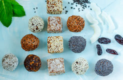 Healthy raw energy balls with cocoa, coconut, sesame, chia on a blue background. stock images