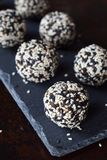 Healthy raw energy bites with flax seeds, almonds, banana and dates. Vegan truffles in sesame seeds on dark background. Homemade. Candy balls. Raw food. Gluten stock photo
