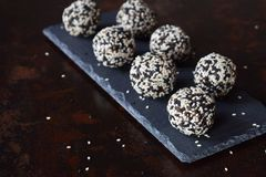 Healthy raw energy bites with flax seeds, almonds, banana and dates. Vegan truffles in sesame seeds on dark background. Homemade. Candy balls. Raw food. Gluten royalty free stock photography