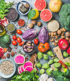 Healthy raw food variety over grey concrete background. Clean eating concept over grey concrete background, top view. Vegetables, fruit, seeds, cereals, beans Royalty Free Stock Images