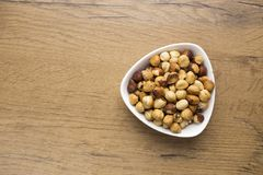 Healthy raw hazelnuts in white bowl on wooden table. Top view of healthy raw hazelnuts in white bowl on wooden table Stock Images