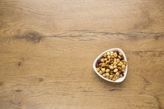 Healthy raw hazelnuts in white bowl on wooden table. Top view of healthy raw hazelnuts in white bowl on wooden table Stock Image