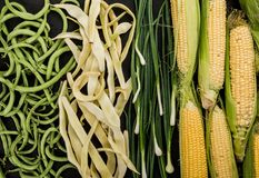 Healthy raw summer vegan vegetables, green and yellow beans, onions, corn cobs on dark stone background. Healthy food, clean eating, top view, flat lay, copy stock photography