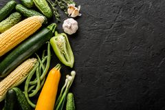 Healthy raw summer vegan vegetables and herbs, cucumbers, corn, pepper, zucchini, green beans on black stone background. Healthy food, clean eating, top view royalty free stock images