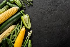 Healthy raw summer vegan vegetables and herbs, cucumbers, corn, pepper, zucchini, green beans. On black stone background. Healthy food, clean eating, top view stock image