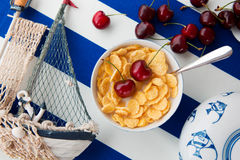 Breakfast. Still life in sea style: cup with a spoon and corn flakes, scattered cherries, wooden model of a ship and blue fishes drawn on a plate Royalty Free Stock Photo