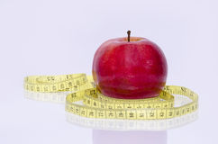 Healthy red apple and a measuring tape. Isolated royalty free stock images