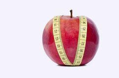 Healthy red apple and a measuring tape. Isolated stock photography