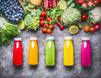 Healthy red, orange, green, yellow and pink Smoothies and juices in Bottles on grey concrete background with fresh organic vegeta. Bles , fruits and berries stock image