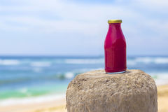 Healthy red smoothie with beach Stock Image