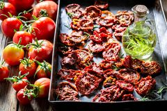 Healthy and red tomatoes dried on baking tray. On wooden table royalty free stock photo