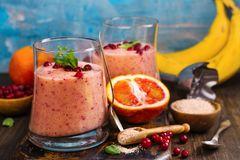 Healthy refreshing pink smoothie with apple, red oranges, cowberry and bran. With ingredients on wooden table. Copy space Stock Images