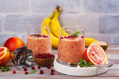 Healthy refreshing pink smoothie with apple, red oranges, cowberry and bran. With ingredients on wooden table. Copy space Royalty Free Stock Photos