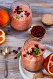Healthy refreshing pink smoothie with apple, red oranges, cowberry and bran. With ingredients on wooden table. Copy space Royalty Free Stock Images