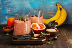Healthy refreshing pink smoothie with apple, red oranges, cowberry and bran. With ingredients on wooden table. Copy space Royalty Free Stock Photography