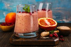 Healthy refreshing pink smoothie with apple, red oranges, cowberry and bran. With ingredients on wooden table. Copy space Stock Photography