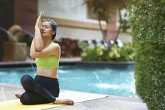Healthy and Relaxation concept. Asian woman practicing yoga pose. Or pilates and sitting near swimming pool stock photography