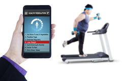 Healthy resolutions app with man runs on treadmill Stock Photos
