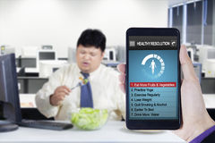 Healthy resolutions app and overweight worker. Image of hand holding smartphone with healthy resolutions program and overweight businessman eats salad in office Royalty Free Stock Photos