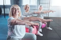 Mature ladies enjoying training session at gym. Healthy retirement. Motivated elderly ladies beaming while sitting on colorful fitness balls with their hands stock image