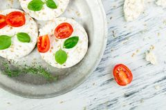 Healthy Rice Cakes. Healthy Rice Cakes with cherry tomatoes, cheese feta, basil and sesame in metal plate on white background. Diet snack. Top view royalty free stock photo