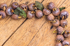 Healthy ripe Medlars on the old wooden table Stock Photos