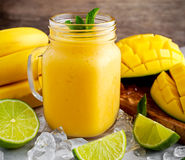 Healthy ripe Yellow Banana Mango Smoothie with slices of Lime, mint and ice Royalty Free Stock Image
