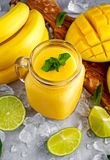 Healthy ripe Yellow Banana Mango Smoothie with slices of Lime, mint and ice. concept healthy food Royalty Free Stock Photography