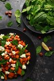 Healthy roasted sweet potato salad with spinach, feta cheese, hazelnut nuts in black plate.  royalty free stock photography