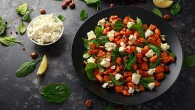 Healthy roasted sweet potato salad with spinach, feta cheese, hazelnut nuts in black plate.  stock photo