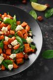 Healthy roasted sweet potato salad with spinach, feta cheese, hazelnut nuts in black plate.  stock image