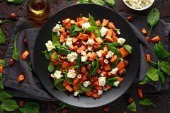 Healthy roasted sweet potato salad with spinach, feta cheese, hazelnut nuts in black plate, rustic background.  stock photos