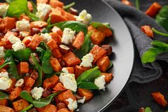Healthy roasted sweet potato salad with spinach, feta cheese, hazelnut nuts in black plate, rustic background stock image