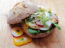 Healthy roll with poached eggs and vegetables Royalty Free Stock Photo