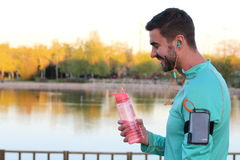 Healthy runner taking a break to drink some water.  Stock Photography