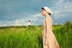 The healthy rural life. The woman and man in the green field. The healthy rural life. The women in kerchief and men in hat against green meadow Stock Photos
