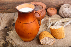 Healthy rustic breakfast. Milk in jug and bread on wooden table Stock Images