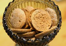 Black Glass Bowl Filled with Rye Chips. Healthy rye bread chips in a dark glass bowl that`s on a wooden surface. These crackers are a something that Finish stock image