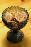 Black Glass Bowl Filled with Rye Chips. Healthy rye bread chips in a dark glass bowl that`s on a wooden surface. These crackers are a something that Finish stock photo