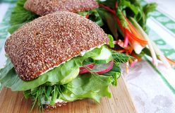 Healthy rye bread sandwich with radish. Big healthy rye bread sandwich with fresh with radish, cucumber, green vegetables and herbs on a wooden kitchen board Stock Photography