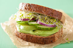 Healthy rye sandwich with avocado cucumber alfalfa sprouts.  stock photos
