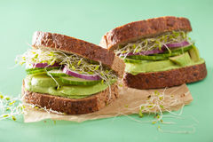 Healthy rye sandwich with avocado cucumber alfalfa sprouts Stock Photo