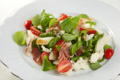 Healthy salad. Delicious salad with fresh greens, tomatoes, roquefort and pear Stock Photos