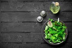 Healthy salad. Arugula salad in a bowl. On a black rustic background stock photo